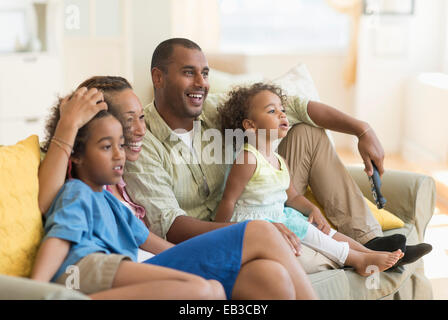 Family watching television together in living room - Stock Photo