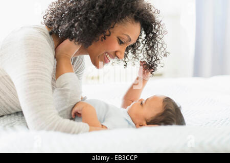 Mixed race mother holding baby on bed