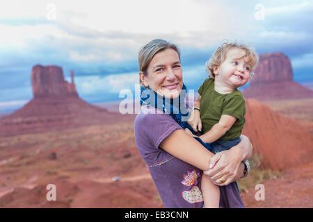 Caucasian mother holding baby son in desert, Monument Valley, Utah, United States - Stock Photo