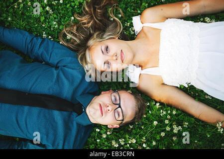 USA, Minnesota, Hennepin County, Minneapolis, Overhead view of young couple lying on grass - Stock Photo