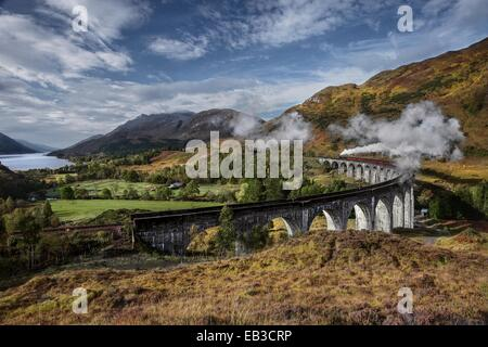 UK, Scotland, Elevated view of Jacobite Express crossing Glenfinnan Viaduct - Stock Photo