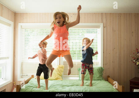 Caucasian children jumping on bed - Stock Photo