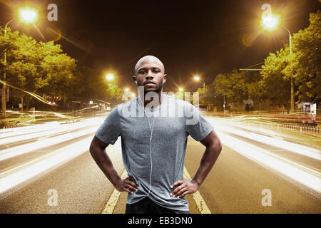 Time lapse view of Black runner standing on city street at night