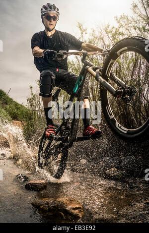USA, Colorado, Mountain biker riding through stream - Stock Photo