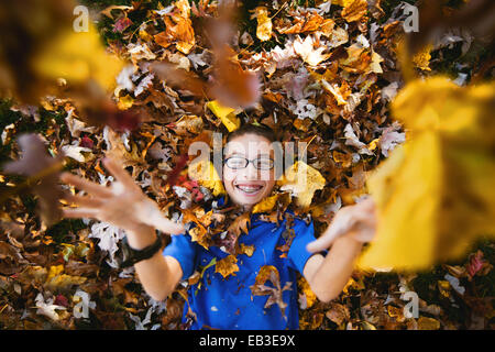 USA, Maryland, Howard County, Dayton, Boy laying on back and playing with autumn leaves - Stock Photo