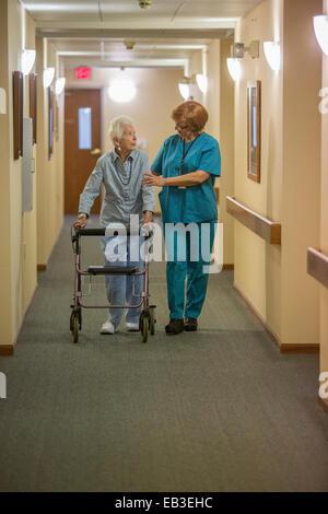Older Caucasian woman walking with nurse in nursing home - Stock Photo