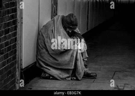 Homeless vagrant begging at the entrance to a London subway. - Stock Photo