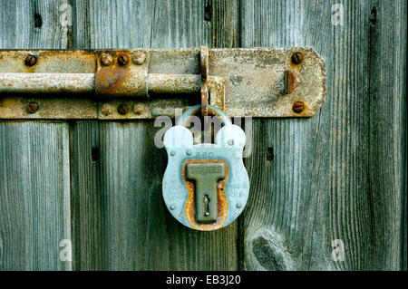 OLD PADLOCK MADE FROM METAL LOCKING AN OLD BOLT ON A WOODEN DOOR - Stock Photo