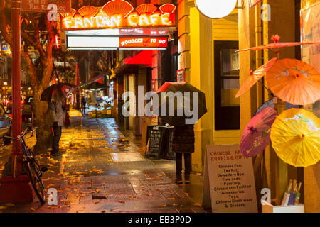 Chinese couple at Fan Tan alley entrance in Chinatown on rainy night-Victoria, British Columbia, Canada. - Stock Photo