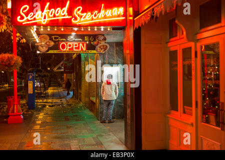 Young man reading menu outside Chinese restaurant in Chinatown on rainy  night-Victoria, British Columbia, Canada. - Stock Photo
