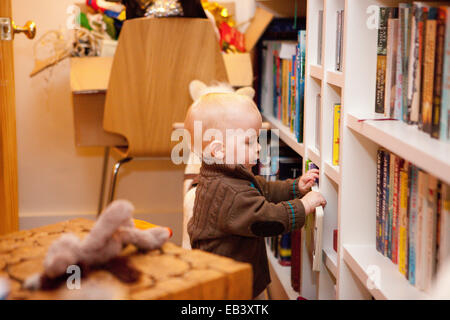 Baby picking a book from book shelf - Stock Photo