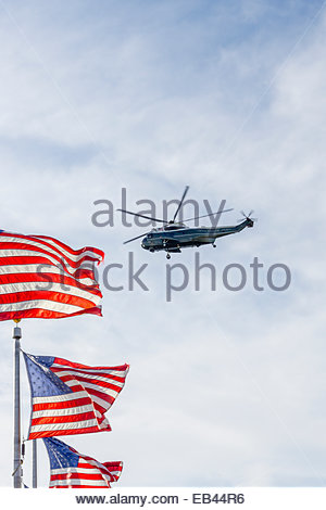 A helicopter from the US presidential fleet flies over the US flags around the Washington Monument in Washington, - Stock Photo
