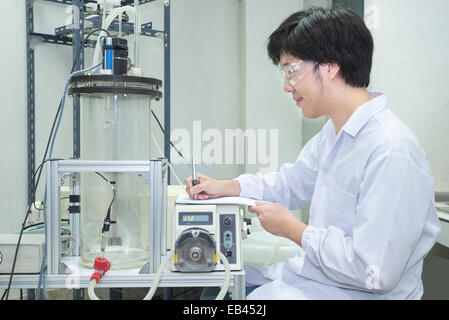 Scientist conducting research taking notes  in laboratory - Stock Photo