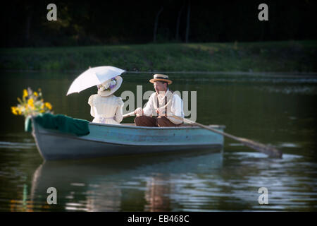 An Old Fashioned couple rowing a boat on a date - Stock Photo