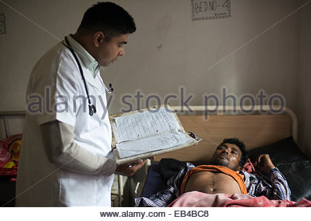 A doctor consults a patient in a rural hospital in Nepal - Stock Photo