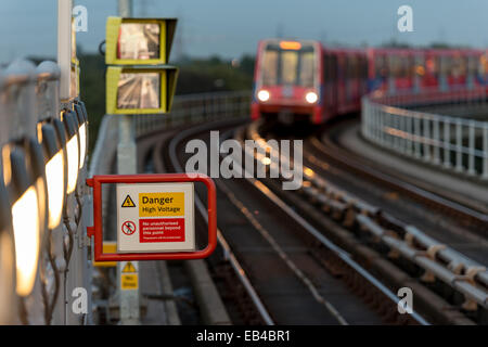 Electricity warning: Danger High Voltage sign on Docklands Light Railway platform in East London - Stock Photo