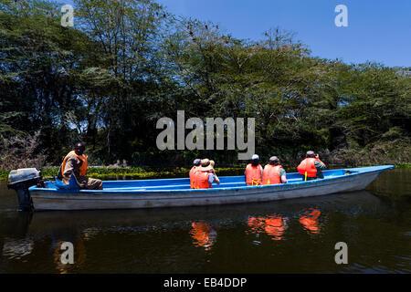 Tourists wearing life-jackets explore the shoreline of Lake Naivasha in a motorboat. - Stock Photo