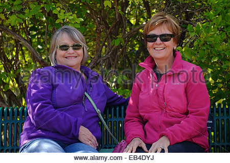 Two mature women smile as they enjoy a nice day in the Daniel Stowe Botanic Garden. - Stock Photo