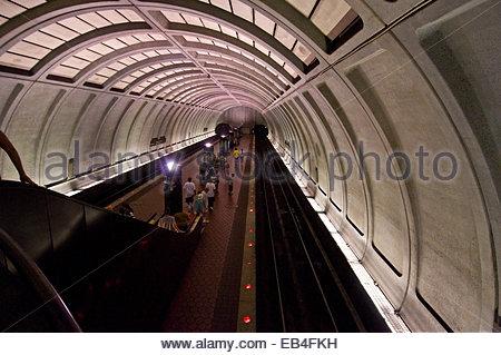 Passengers wait for a train on a subway platform. - Stock Photo