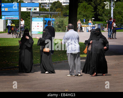 Arab Saudi Arabian Women tourists in traditional black Burka in Olympia Park Munich Germany Europe - Stock Photo