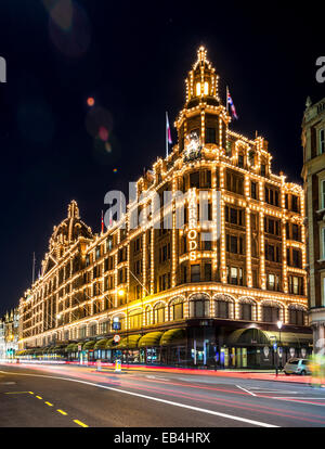 Harrods is a world famous department store in Kinightsbridge; it is lit up spectacularly at night - Stock Photo