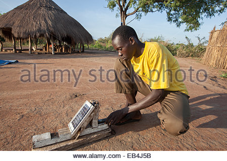 A young man uses a solar charger to power his mobile device. - Stock Photo