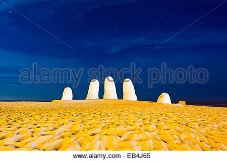 Yellow light at night creating a strange landscape at The Hand, or Mano de Punta del Este, created in 1982 by Chilean - Stock Photo