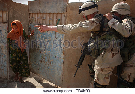Soldiers from the 1st Squadron, 2nd Armored Cavalry Regiment order an Iraqi girl from her home before they enter - Stock Photo