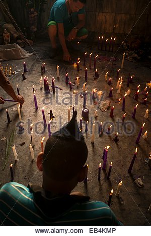 Pilgrims light candles in the Church of San Lazaro on December 17, the feast day of San Lazaro. - Stock Photo