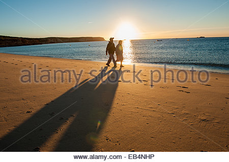 A couple strolling at sunrise along Martinhal Beach in Sagres, Algarve, Western Portugal. - Stock Photo