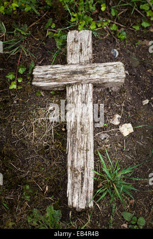Wooden Cross Laying On The Ground With Three Nails Nearby