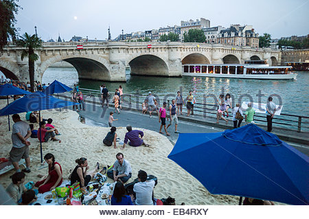 Parisians and tourists at Paris Plage, an artificial, temporary beach on the bank of the Seine River. - Stock Photo