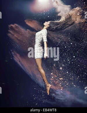 Slim, fit ballet dancer among the dust - Stock Photo
