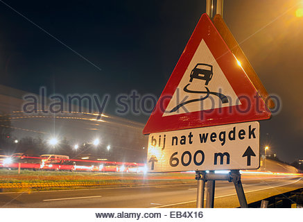 Amsterdam The Netherlands slippery when wet sign at night. Road safety. - Stock Photo