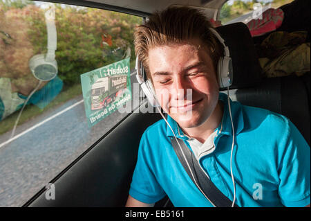 A 14 year old boy listening to music in the car - Stock Photo