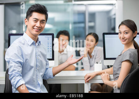 Portrait of young businessman and businesswoman in office - Stock Photo
