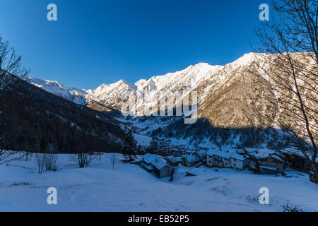 Winter landscape at sunrise over alpine valley and cold snowcapped village in the ski resort of Praly, Piedmont, - Stock Photo