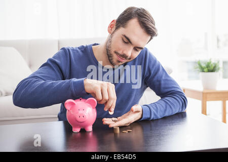 Young man putting coins in piggy bank - Stock Photo