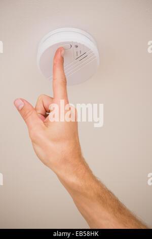 Handyman testing smoke detector - Stock Photo