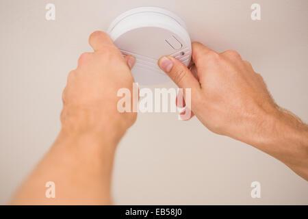 Handyman installing smoke detector - Stock Photo