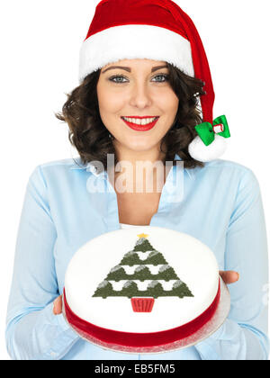 Confident Young Woman Wearing A Red Santa Hat Holding A Rich Iced Christmas Fruit Cake Isolated Against A White - Stock Photo