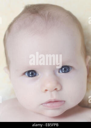 A nine week old baby girl with blue eyes. - Stock Photo