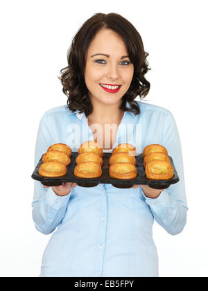 Attractive Young Woman Holding A Tray of Cooked Yorkshire Puddings - Stock Photo