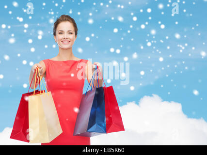 smiling elegant woman in dress with shopping bags - Stock Photo