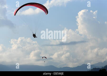 Paragliders fly the skies over Phewa tal-lake after jumping from the lesser slopes of the Annapurnas range-Himalayas - Stock Photo
