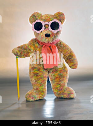 A teddybear dressed in sunglasses and carrying a cane - Stock Photo