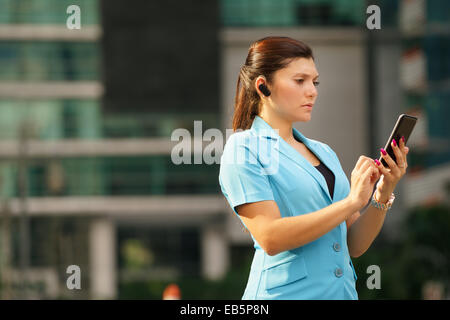 Adult hispanic person with mobile phone and wireless bluetooth headset, talking on telephone in the street out office - Stock Photo