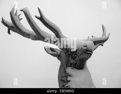 Snow covered statue of a red deer stag on Bowood country estate in Wiltshire, UK - Stock Photo
