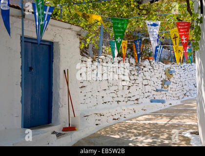 Kioni, Ithaca, Ionian Islands, Greece. Colourful religious pennants hanging above typical whitewashed village alley. - Stock Photo