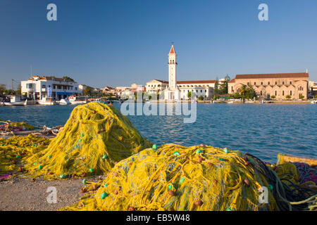 Zakynthos Town, Zakynthos, Ionian Islands, Greece. View across harbour to the cathedral, fishing nets piled up on - Stock Photo